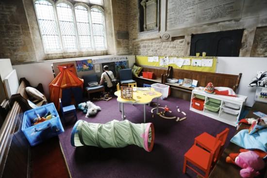 Kinderspielplatz mit großem Kind in einer protestantischen Kirche in England