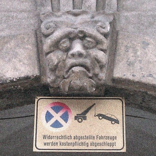 Trauriges Gesicht über Hauseingang in Graz, Falschparken macht traurig