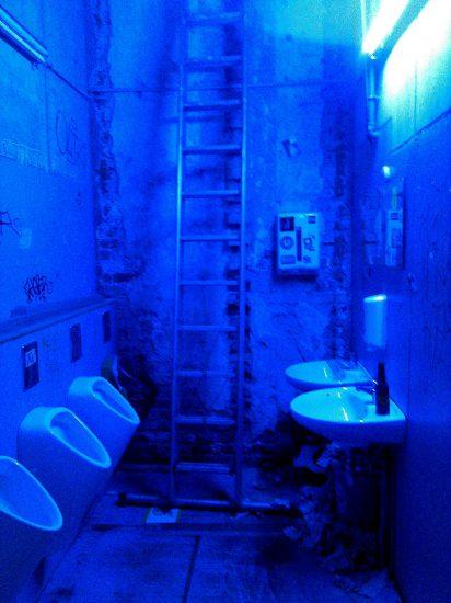 Blau beleuchteter Toilettenraum mit Leiter