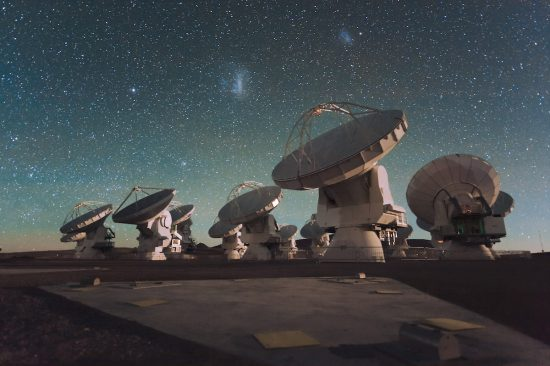 Die Antennen des Atacama Large Millimeter/submillimeter Array (ALMA), am Chajnantor Plateau in den Chilenischen Andes. Die beiden Magellanschen Wolken photobomben im Hintergrund… (via Wikimedia Commons)